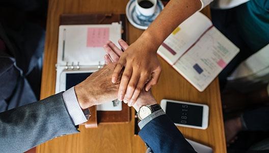 hands together across a desk